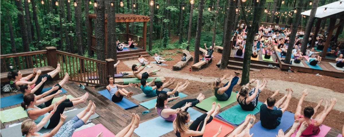 outdoors_yoga_class_stretching_in_sync